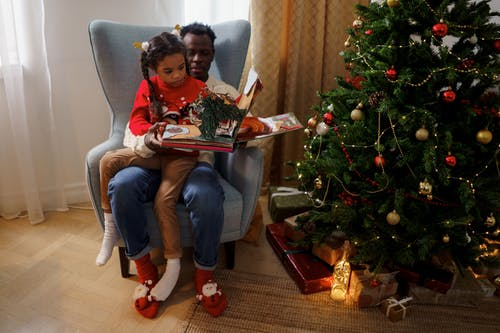 Dad and Daughter Reading a Fairy Tale Book While Sitting Beside a Christmas Tree