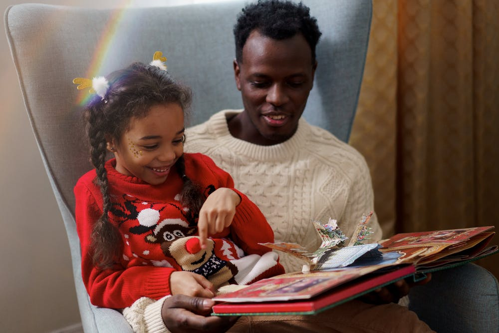 Father and daughter having fun while reading a fairy tale book. | Photo: Pexels