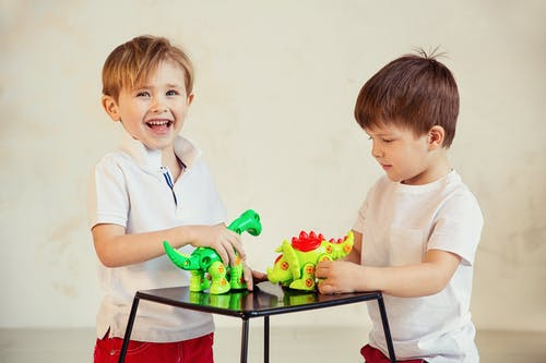 Boy in White Polo Shirt Holding Green and White Plastic Toy
