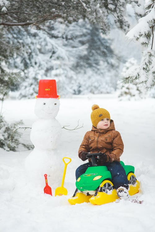 Child in Brown Jacket Riding on Blue and Red Ride on Toy Car on Snow Covered