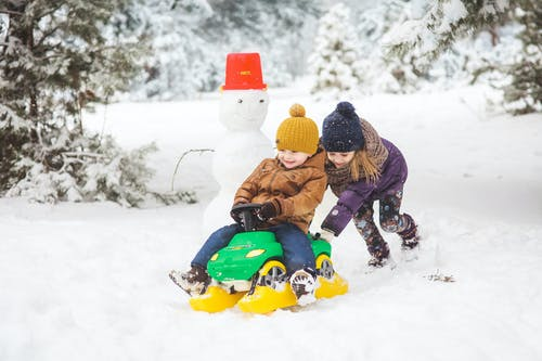 Child in Brown Jacket Riding on Green and Yellow Ride on Toy Car on Snow Covered