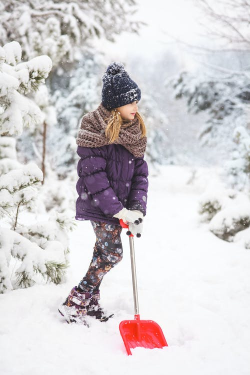 Woman in Black Jacket and Black Knit Cap Holding Ski Pole on Snow Covered Ground during