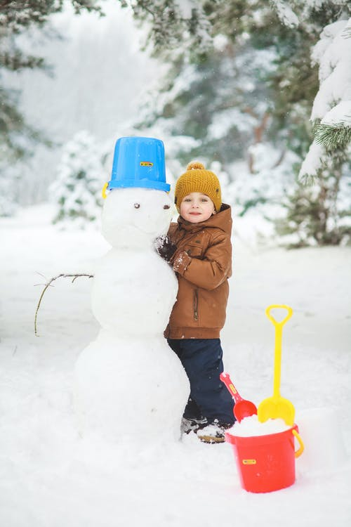 Girl in Brown Jacket and Blue Pants Holding White Snowman