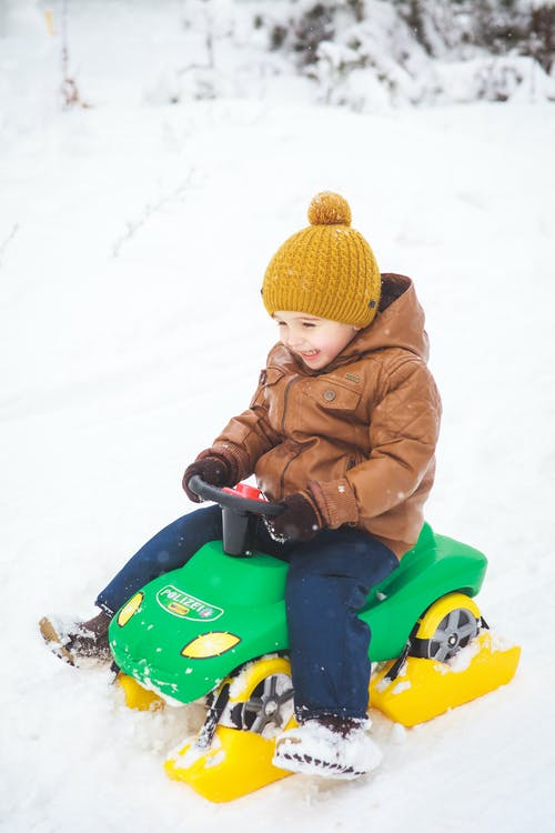 Child in Brown Jacket Riding on Green and Black Ride on Toy Car on Snow Covered