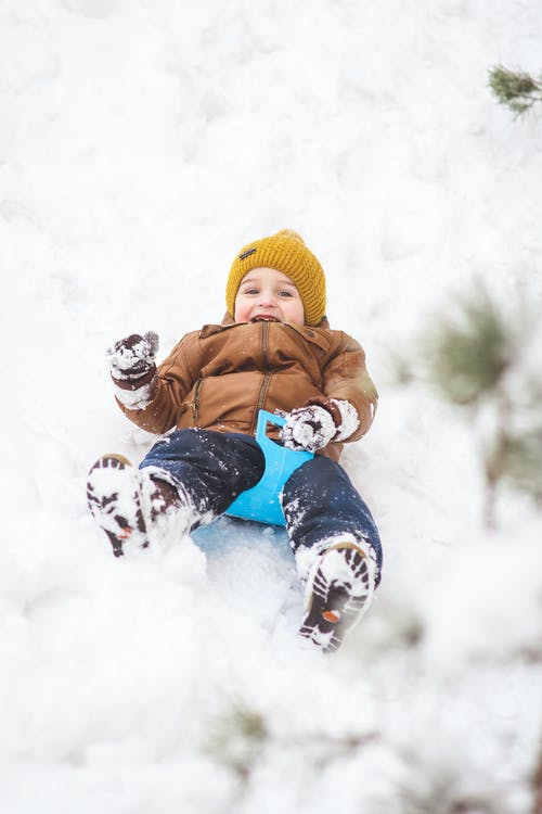 2 Children in Red Jacket and Yellow Knit Cap Playing on Snow