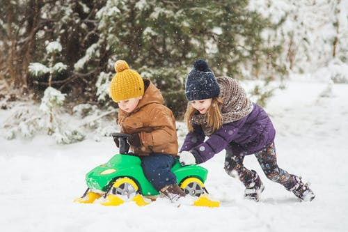 Child in Brown Jacket Riding Blue and Green Plastic Sled on Snow Covered Ground