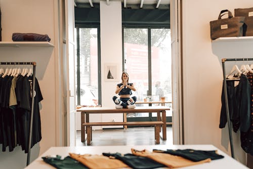 Stylish female in sportswear sitting with crossed legs during meditation and looking at camera on table in boutique with apparel on racks