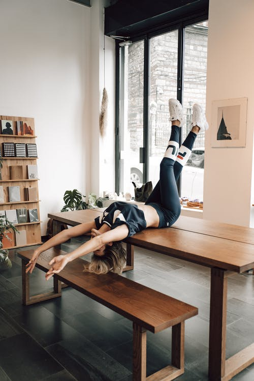 Unrecognizable sportswoman in trendy active wear on table in house