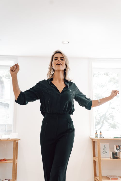 Cheerful woman in black wear dancing in house