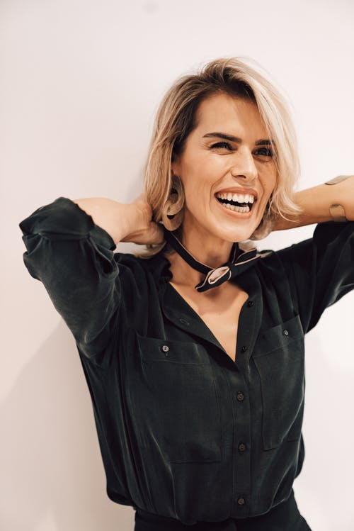 Laughing woman putting on bow tie
