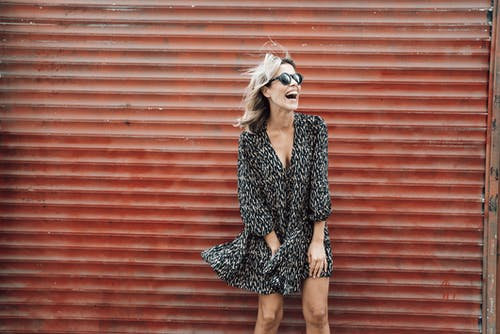 Cheerful female in stylish sunglasses and dress fluttering in wind laughing happily while standing against metal wall