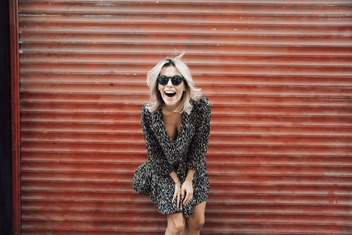 Stylish positive woman in sunglasses laughing brightly