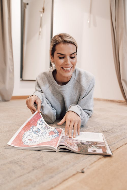 Positive female flipping pages of magazine while reading article at free time at home