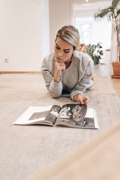 Smart woman reading magazine while resting at home