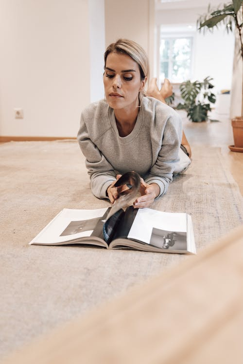 Serious female spending pastime at home and reading magazine while lying on floor in modern apartment