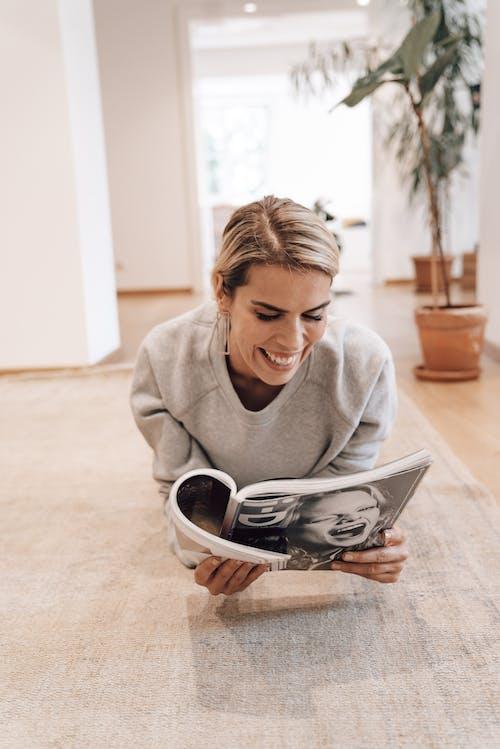 Cheerful woman reading magazine on floor