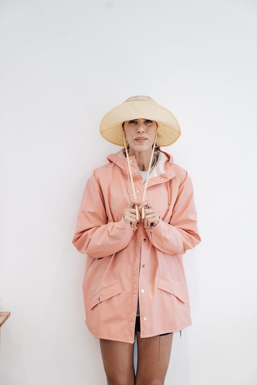 Woman in coat and hat against white wall