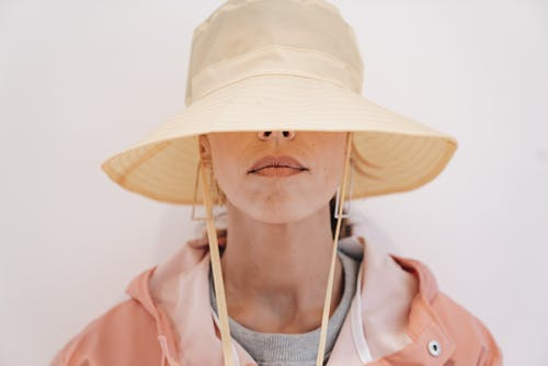 Serious female in outerwear and earrings hiding face with stylish hat against white background