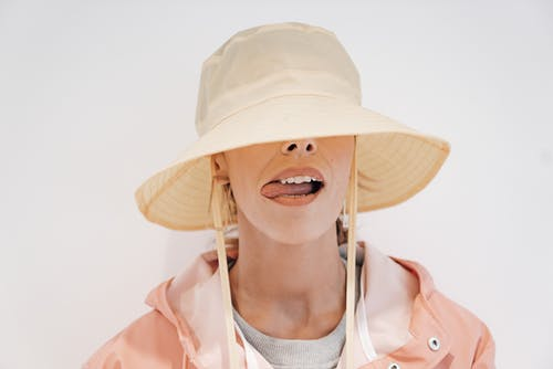 Stylish woman in hat with tongue out