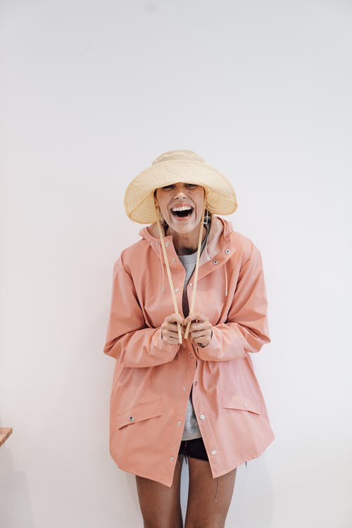 Excited woman in panama hat on white background