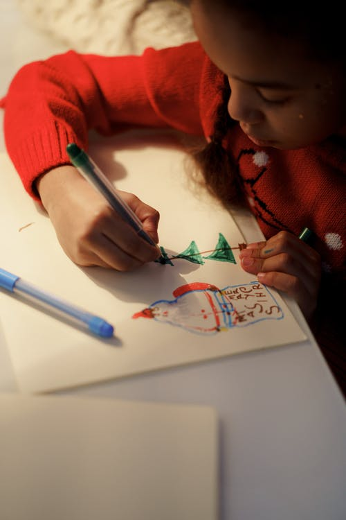 Girl in Red Sweater Making a Christmas Letter