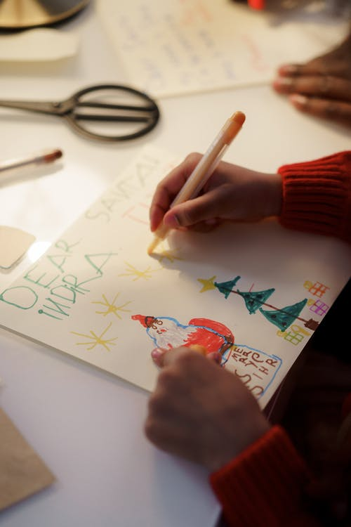 A Person in Red Sweater Making a Christmas Letter