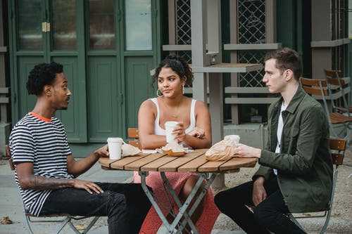 Young multiethnic friends in casual outfits drinking takeaway coffee and eating pastries while sitting at wooden table in street cafe