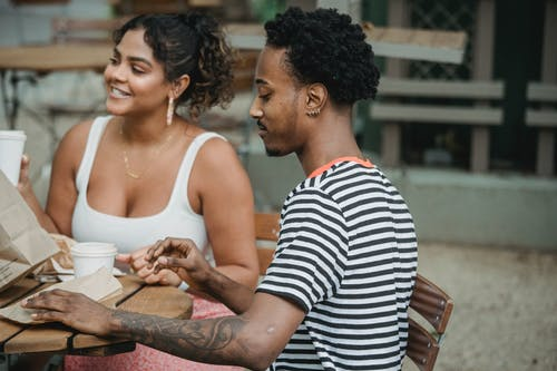 Happy young Hispanic woman and African American man in casual clothes resting on cafe terrace and drinking takeaway coffee during date