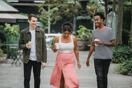 Joyful young diverse friends walking in park and smiling with coffee to go