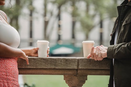 Side view of crop anonymous young couple in casual clothes standing on balcony with cups of coffee to go and chatting