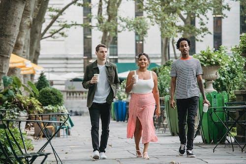 Trendy diverse students walking in park and enjoying takeaway coffee