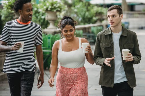 Joyful young multiethnic students in casual clothes discussing lessons while walking together in park with takeaway cups of coffee
