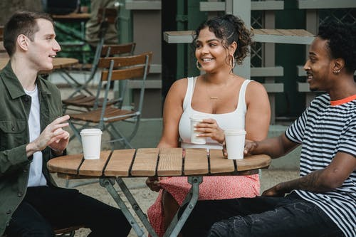 Cheerful young multiracial friends in casual clothes smiling while resting in outdoor cafe with cups of takeaway coffee and communicating