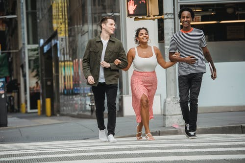 Full body of cheerful young Hispanic lady in stylish clothes holding hands of smiling diverse male friends while crossing road in modern city