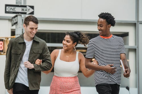 Happy Hispanic woman holding arms of diverse male friends while crossing road