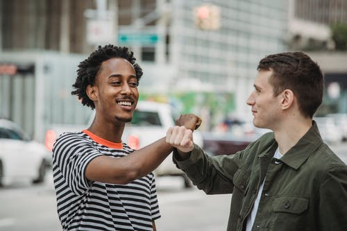 Cheerful young diverse male friends in casual clothes bumping arms and smiling while greeting each other on modern city street