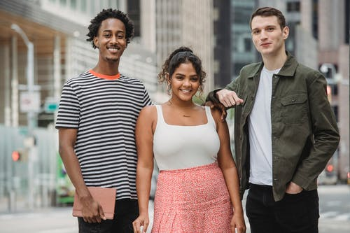 Cheerful young multiracial students in stylish outfits smiling and looking at camera while standing together on modern city street near skyscrapers