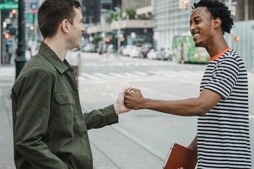 Joyful young multiethnic guys shaking hands on city street