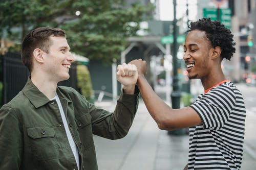 Side view of joyful young multiracial male friends in casual outfits smiling while bumping arms after meting on city street