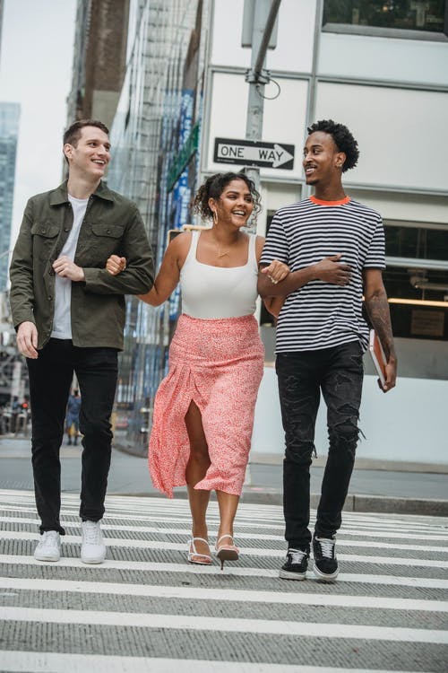 Trendy young multiracial friends having fun while crossing road