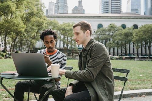 Mann In Der Grünen Jacke, Die Auf Stuhl Mit Macbook Sitzt
