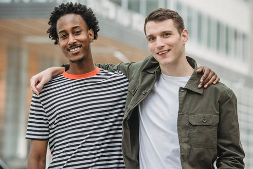 Positive young diverse guys standing on street with hands on shoulders
