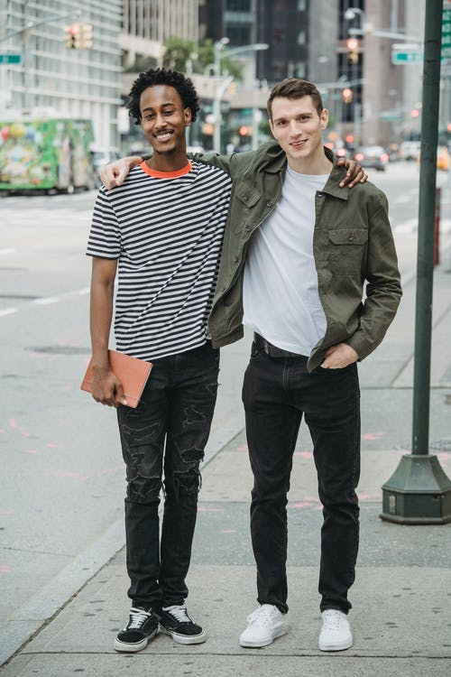 Full body of young multiracial guys in stylish clothes standing on city street with hands on shoulders and smiling at camera