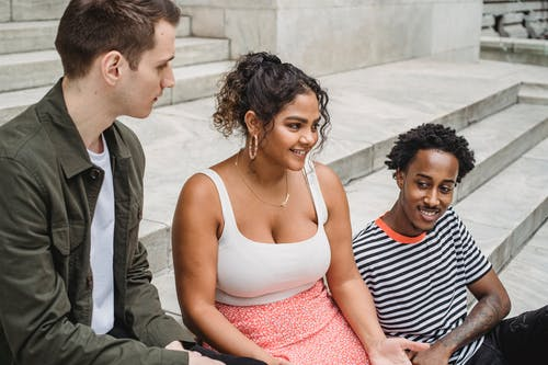 High angle of cheerful young multiethnic friends in casual outfits resting on stairs on city street and chatting