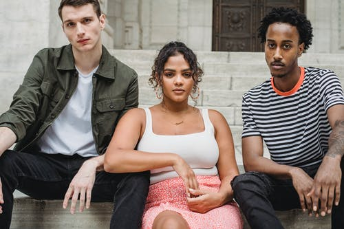 Serious young multiethnic millennials chilling on aged building steps