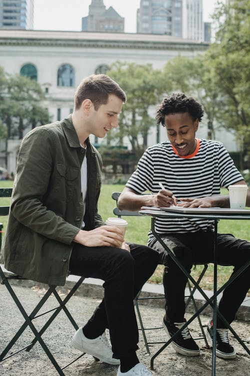Positive young multiracial male students writing in notebook while preparing for exams sitting at table in campus park