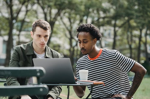 Concentrated young multiethnic male colleagues in casual clothes sitting in outdoor cafe and working remotely on laptop during coffee break