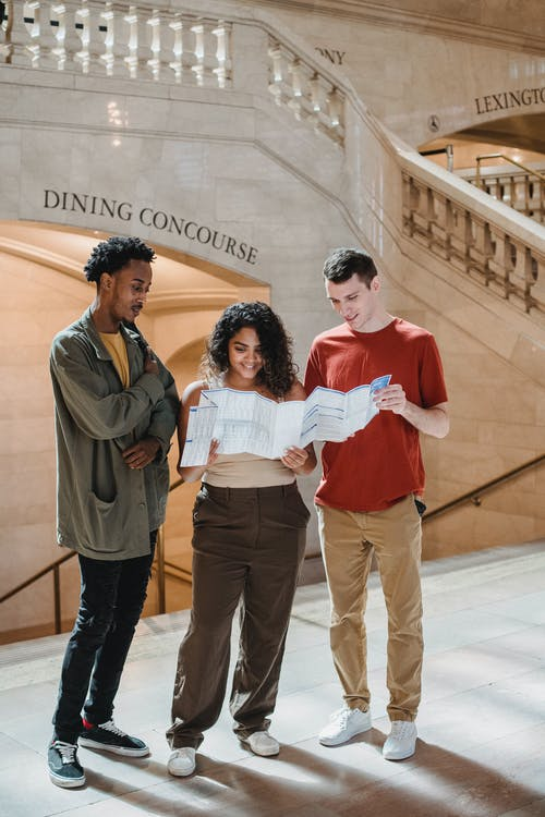 Full body of positive young multiracial friends reading map while standing near stairway in Grand Central Terminal during trip in New York