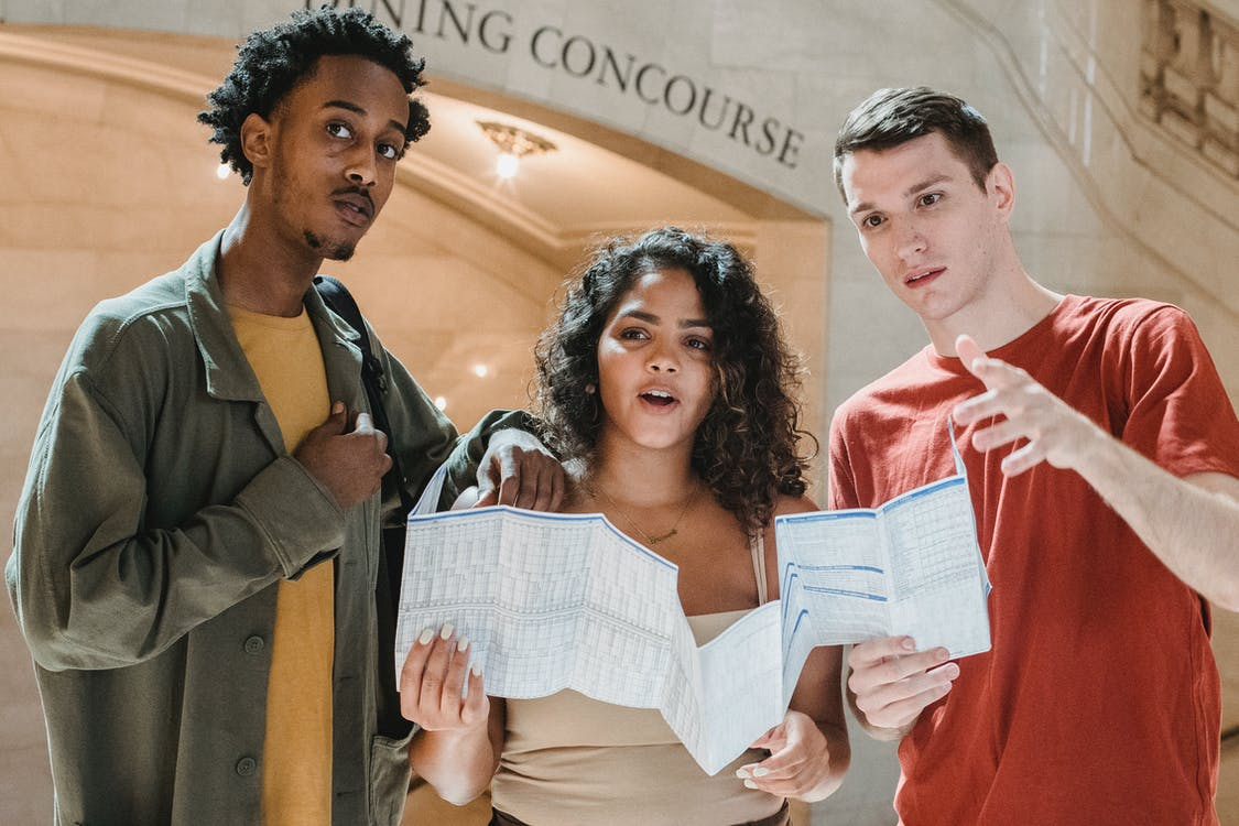 Amazed young multiracial male and female friends in casual outfits looking away while exploring map in Grand Central Terminal