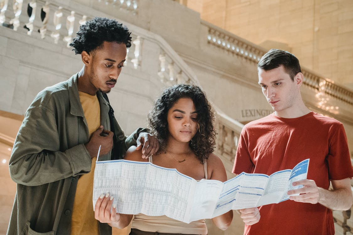 Serious young diverse millennials reading map in railway station terminal